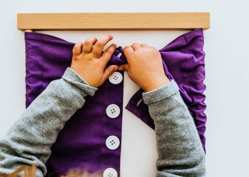 Hand of a student handling montessori material inside a classroo